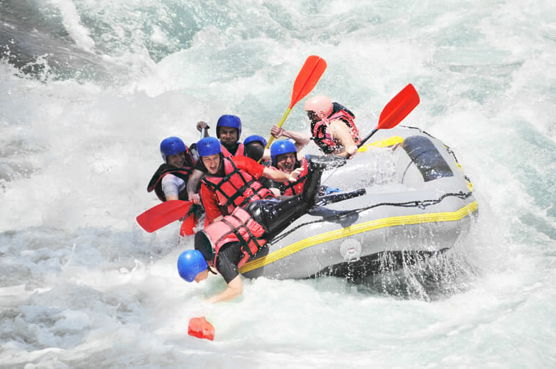 photo of whitewater raft tipping over
